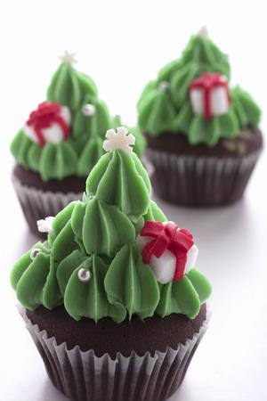 weihnachtskuchen: Weihnachtsbaum Cupcake Dekoration mit Geschenk-Box auf weißem Hintergrund Lizenzfreie Bilder