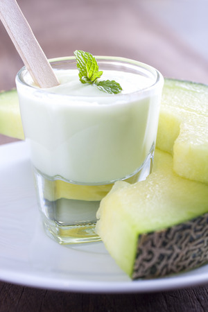 Melon yogurt decorate with mint leaves served with melon slices  photo