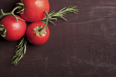 Tomatoes on the wood background with text space Фото со стока