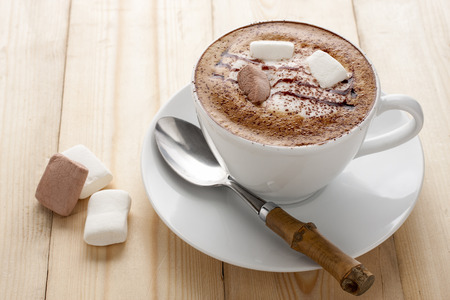 crema: Hot coffee mocha served in a white cup with marshmallow on a wooden table
