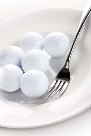 golf balls with a fork on the white plate Фото со стока