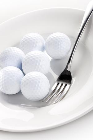 golfballen met een vork op de witte plaat Stockfoto