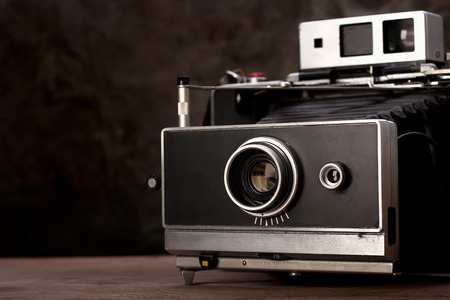 Old vintage camera on wooden table with copy space. photo