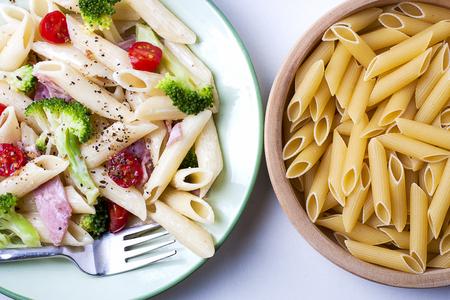Kleurrijke gezonde pasta en ruwe pasta in een houten schotel. Stockfoto
