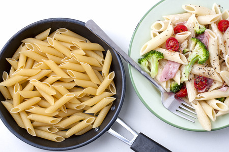 Colorful healthy pasta and raw pasta in a small pan.