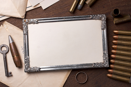 Vintage frame on wooden table and element of the war.