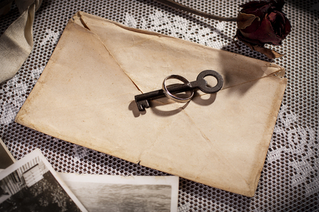 Conceptual of love secrets with vintage envelope , wedding ring and key.