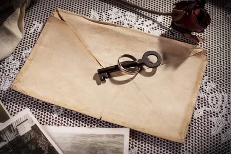 Conceptuele van liefde geheimen met vintage envelop, trouwring en sleutel.