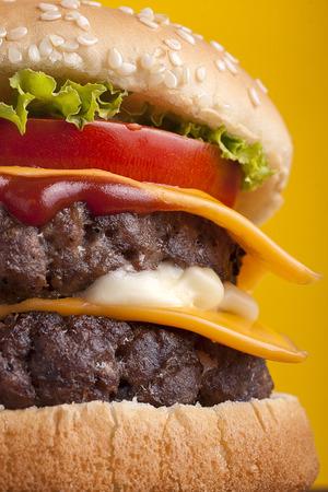 Close-up van Double Cheeseburger op gele achtergrond.
