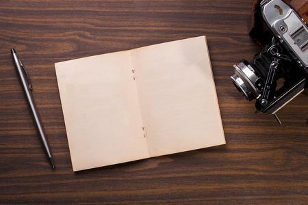 Open journal boek en vintage camera en pen.