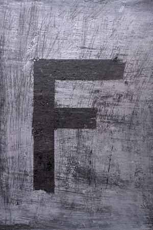 Black grunge alphabet sticky tape effect.Letter F Фото со стока