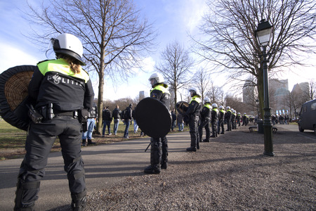 occur: 27 januari 1025 riot police officers watching in line protesters during a demonstration on the Malieveld in The Hague Holland
