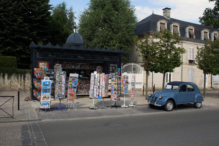 ugly duckling: french streetview with newspapers kiosk and citroen ugly duckling