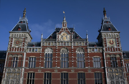weather front: front of the central railway station in Amsterdam, in the towers there are a clock and an weather vane