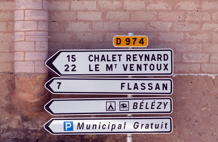 bedoin: bedoin,france-june 28, 2015: road sign to the mont ventoux  and chalet reynard in the village of bedoin