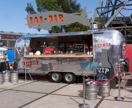 vendor: Amsterdam,Netherlands-july 31, 2015: airstream caravan in use as a food truck in use as a bar in Amsterdam