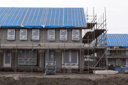 concrete commercial block: Amsterdam, Netherlands-januari 3, 2016: A house under construction with scaffolding in new neighborhood in Amsterdam Editorial