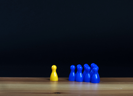 pawns: ilsolated yellow pawn and group of blue pawns on a table Stock Photo
