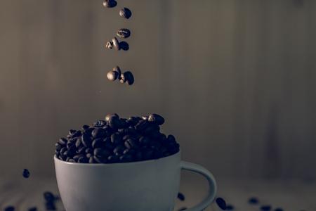 コーヒー豆は、木製の背景、効果フィルター低キー照明とカップのしずくです。