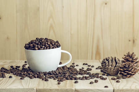 coffee beans in cup with wooden background and effect filter. decorate with pine cone background. Stock Photo