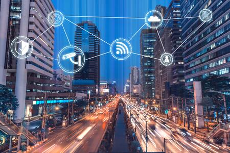 Arquitetura da cidade do centro na noite, no tráfego e no muito ícone na cidade, fundo da tecnologia sobre o Internet do conceito da coisa.