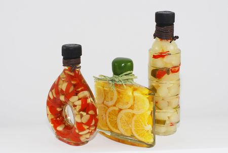 3 gourmet glass bottles filled with olive oil, peppers, lemon slices and onions