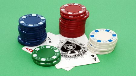 colored stacks of poker chips on a pair of aces against a green background Editorial