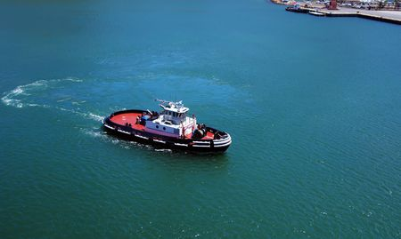tugboat: A tugboat cruising in the blue waters of the ocean