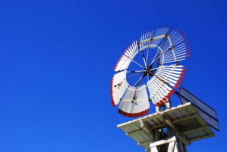 White Farm Windmill against a clear blue sky Stock Photo