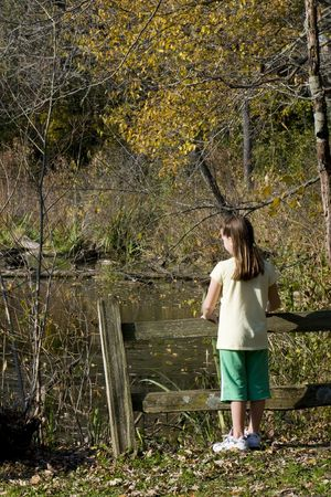 Young girl standing by a fence overlooking a lake