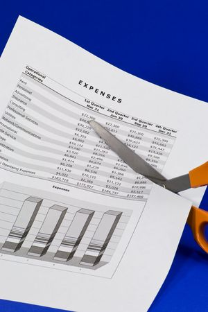 A scissors cutting a spreadsheet of expenses