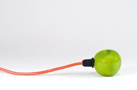 それに接続されている電気コードとグリーンアップル
