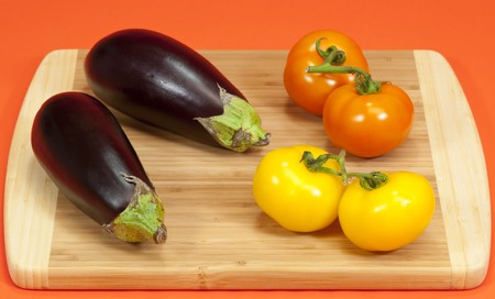 Fresh ripe eggplant and vine ripe tomatoes on a wooden cutting board Stock Photo