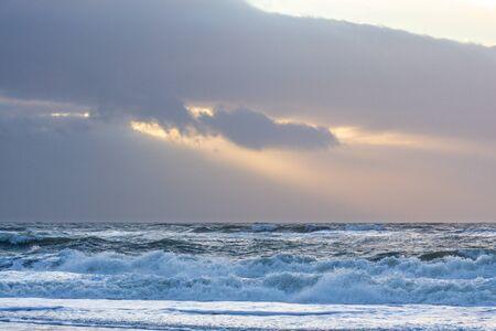 Sunbeams breaking through dark clouds above churning North Sea