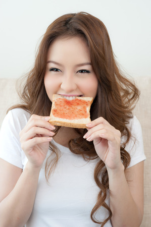 Happy Young Woman Eating Bread and jam