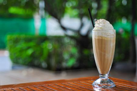 정원 배경에서 상단에 아이스 커피의 유리와 크림
