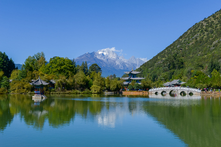Black Dragon Pool to the Five Phoenix Tower and the Five Holes Bridge. In the background is Jade Dragon Snow Mountain. The Old Town of Lijiang is located in Lijiang City, Yunnan, China. Stock Photo