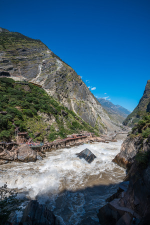 perilous: Tiger Leaping Gorge near Lijiang Ancient Town, Lijiang Attractions. One of the deepest canyons in the world r there is a rock in the middle of Golden Sand River called Tiger Leaping Rock in Hu Tiao Xia, Lijiang, Yunnan, China Stock Photo