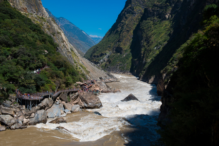 Tiger Leaping Gorge near Lijiang Ancient Town. One of the deepest canyons in the world. A rock in the middle of Golden Sand River called Tiger Leaping Rock in Lijiang, Yunnan, China