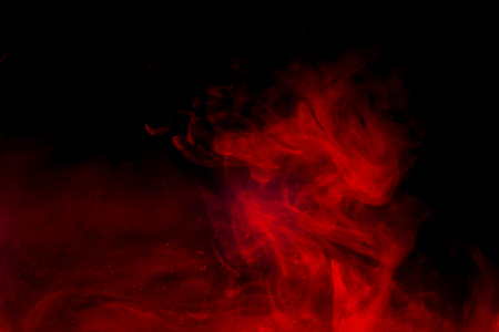 Red smoke isolated on black background.