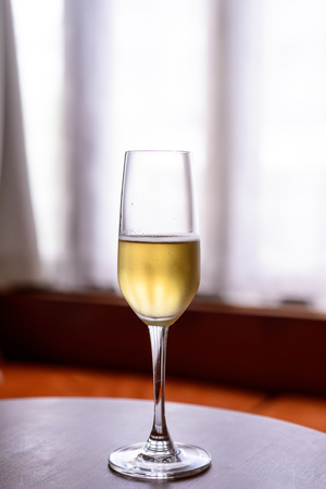 champagne glass with blurred curtain background