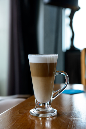 Layer cappuccino coffee in a clear glass mug on wooden table 写真素材