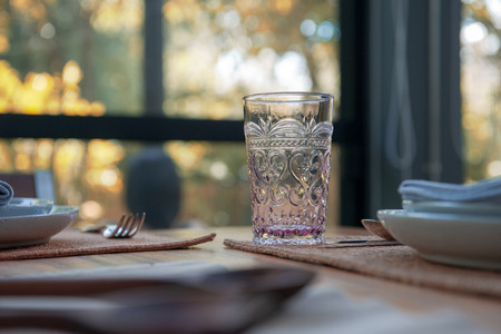 Dinner Table setting with Glasses and plates on table in restaurant