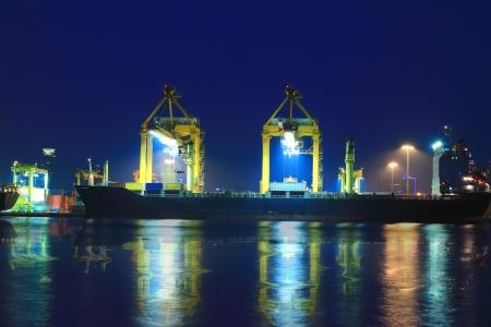 夜にコンテナーを積む貨物船