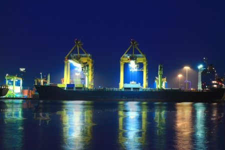 Vrachtschip laden containers per nacht Stockfoto