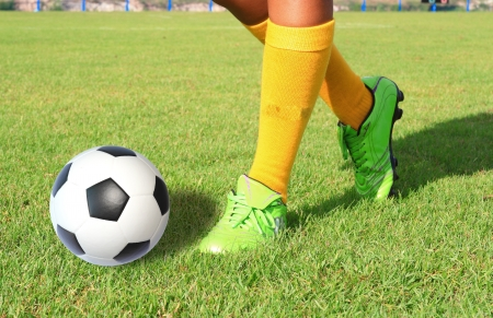 grassfield: soccer ball with foot of player kicking it