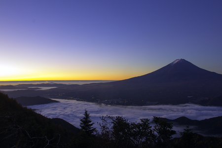 Mount Fuji enshrouded in clouds with clear sky from lake kawaguchi, Yamanashi, Japan Stock Photo