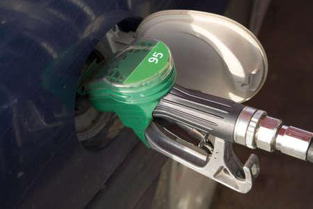 unleaded: Gasoline pump nozzle in automobile gas tank