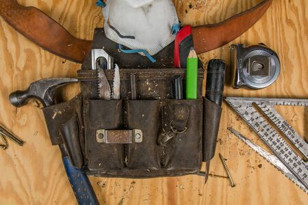 Authentic genuine used construction carpentry tools and leather tool belt or nail bag. Flat lay on wood background with screws, saw blades and saw dust