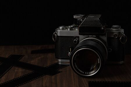 Vintage film camera on a wooden table and black background with film lens and camera shot in low key dark style